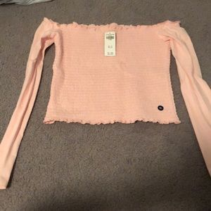 A pink long sleeve top that's off the shoulders